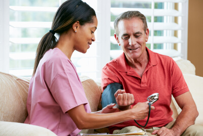 nurse measuring blood pressure of elderly man