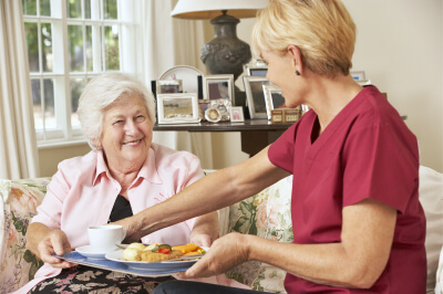 caregiver serving elderly woman