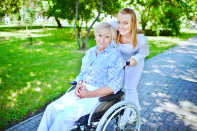 caregiver and senior in a wheelchair smiling